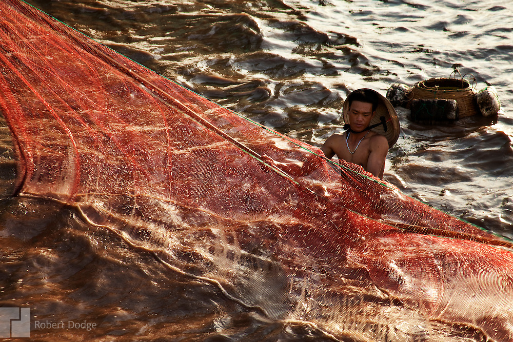 A fisherman battles wind and tide to control his fishing nets in the South China Sea at Bac Lieu Province. Robert Dodge, a Washington DC photographer and writer, has been working on his Vietnam 40 Years Later project since 2005. The project has taken him throughout Vietnam, including Hanoi, Ho Chi Minh City (Saigon), Nha Trang, Mue Nie, Phan Thiet, the Mekong, Sapa, Ninh Binh and the Perfume Pagoda. His images capture scenes and people from women in conical hats planting rice along the Red River in the north to men and women working in the floating markets on the Mekong River and its tributaries. Robert's project also captures the traditions of ancient Asia in the rural markets, Buddhist Monasteries and the celebrations around Tet, the Lunar New Year. Also to be found are images of the emerging modern Vietnam, such as young people eating and drinking and embracing the fashions and music of the West. His book. Vietnam 40 Years Later, was published March 2014 by Damiani Editore of Italy.