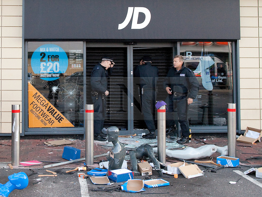 © Licensed to London News Pictures . FILE PICTURE DATED 07/08/2011 . Tottenham , UK . Police peer in through the shutters of JD Sports in Tottenham Retail Park as looters continue to forage inside . During riots in Tottenham the first of several nights of looting took place in Tottenham Retail Park . Photo credit : Joel Goodman/LNP