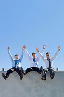 Group of handsome businessmen sitting while having fun in office rooftop