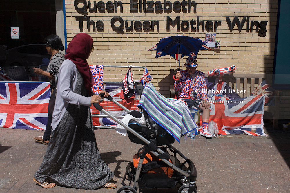 Muslim mother and child passes royalist as tension mounts outside St Mary's Hospital, Paddington London, where media and royalists await news of Kate, Duchess of Cambridge's impending labour and birth. Some have been camping out for up to two weeks during a UK heatwave, having bagged the best locations where an heir to the British throne will eventually be shown to the world.