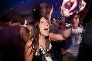 HAPPY PRETTY BRUNETTE GIRL DANCING WAVING HER ARMS CHEERING AND POINTING