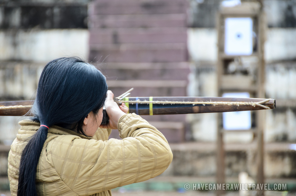 A young Lao woman takes aim with a crossbow in a student crossbow archery contest near Vieng Xai in northeast Laos.