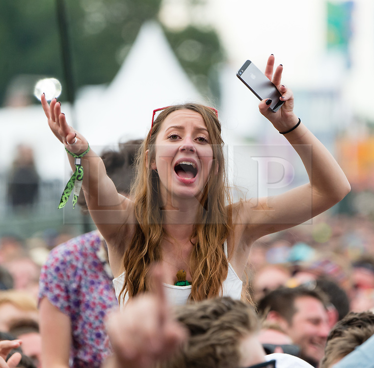 © Licensed to London News Pictures. 14/06/2015. Isle of Wight, UK.  Female festival goers watch  Paolo Nutini perform at Isle of Wight Festival 2015 on Sunday Day 4.  Yesterday suffered torrential rain all afternoon and evening, after a first day of warm sun.  This years festival include headline artists the Prodigy, Blur and Fleetwood Mac.  Photo credit : Richard Isaac/LNP
