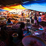 Shoppers stop at stalls to buy vegetables at a traditional market