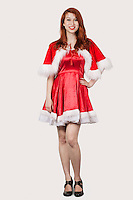Portrait of happy young woman in Santa costume standing against gray background