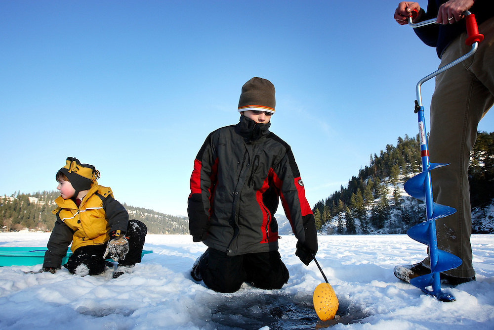 JEROME A. POLLOS/Press..Jackie Barrett, 9, center, scoops ice out of a fishing hole his father Andy Barrett drilled Monday on Fernan Lake. Nicholas Jacklin, 5, left, was enjoying a walk on the 7-inch thick ice with his aunt when the Barrett's ice fishing activity piqued his interest.