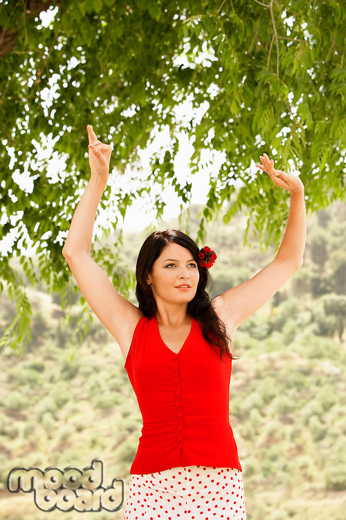 Woman flamenco dancing outdoors front view.