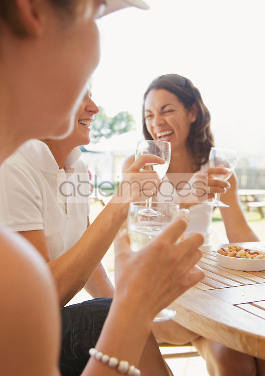 Close up of a group of women drinking and laughing at a restaurant