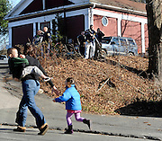 A mother runs with her children as police above canvass homes in the area of Sandy Hook Elementary School after a shooting in Newtown, Conn., Friday, Dec. 14, 2012. (AP Photo/Jessica Hill)