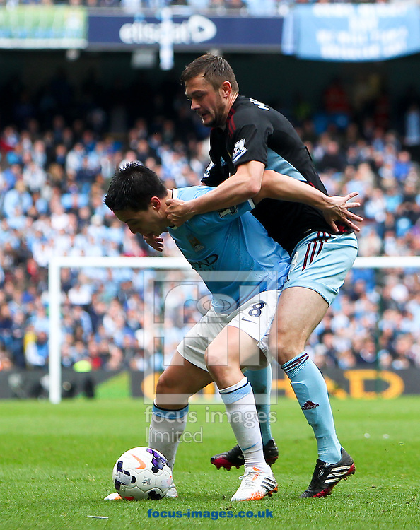 Samir Nasri of Manchester City and George McCartney of West Ham United during the Barclays Premier League match at the Etihad Stadium, Manchester<br /> Picture by John Rainford/Focus Images Ltd +44 7506 538356<br /> 11/05/2014