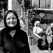 An elderly lady, returning from working the fields pauses with her pick as two friends engage in conversation in the background in the rural district of Maramures,  Romania. Photo Tim Clayton..Romania entered the European Economic Community in January 2007, signaling a fresh exodus of the work force as many Romanians fled the country in search of a better life. Sadly many have not found the employment sought and Romanian communities camped in European cities are making headlines for all the wrong reasons...In a nation recovering from communist rule from 1947 to 1989 and a decade of economic instability and decline that followed, it is estimated Romania has lost between 2.0 and 2.5 million of it's workforce since the end of communist rule. Considering Romanian's population is estimated at 22 million, this is about 10% of the Country's population...Life goes on as normal for those who have remained in Romania. In a country steeped in history and culture there has been little or no change in age old traditions, life is personified in the rural communities where a third of Romanian's population is employed in agriculture and primary production, one of the highest in Europe.