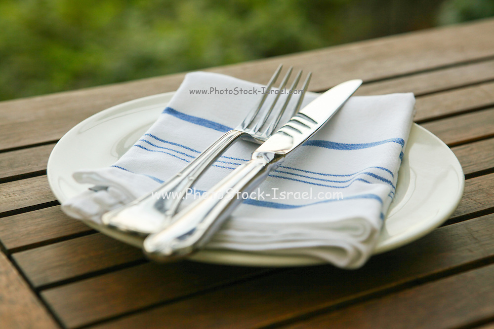 Outdoor hospitality concept plate, serviette, for and knife on a wooden table outdoors