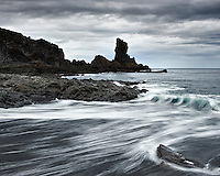 Black pebble beach at Djúpalón Iceland. Dramatic gray clouds. Sandfjara við Djúpalón. Grá ský á himni.