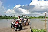 Commuters get off a ferry shuttling between two riverbed sides, Can Tho area, Vietnam, Southeast Asia