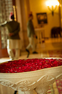 Rose petals in a stone water feature in the hotel lobby of the Leela Palace, with the bellboys in the background. Bangalore, India