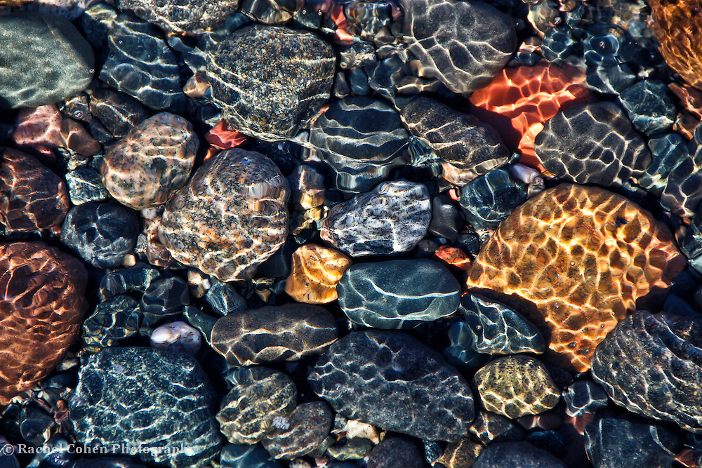 &quot;A Stones Throw&quot; 4<br /> <br /> The underwater glimmer and ripples ride over beautiful Lake Superior stones from the bright sun shining above!!<br /> Brilliant colors of blue, yellow, red, pink, and gray sparkle in the shallow waters!!<br /> <br /> Nature Abstracts by Rachel Cohen