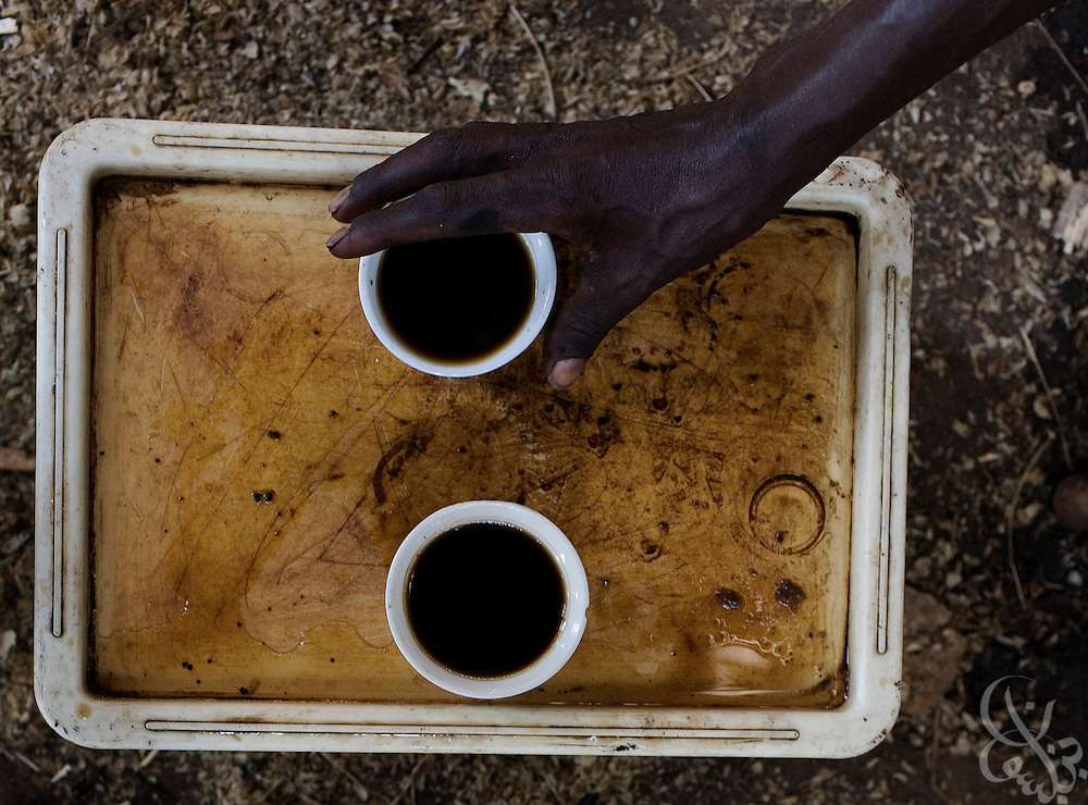 An Ethiopian man reaches for a cup of coffee during a local coffee ceremony February 23, 2007 in Fero, Ethiopia in the famed southern Sidamo coffee region. Ethiopia is the birthplace of arabica coffee, and the coffee ceremony, a process of roasting green coffee beans, grinding them, burning incense and joining together to share a cup that is a daily tradition for many Ethiopians.