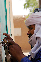 Niger,Agadez,2007. Rissa Ixa locks up Fatima Ixa's traditional handicrafts shop in the center of Agadez.