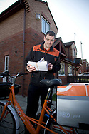John Shimka, a postal delivery worker employed by TNT Post, on his rounds delivering letters to residential properties in the centre of Liverpool. TNT Post are currently running a pilot project in the city to develop an end-to-end postal service to challenge the Royal Mail on their monopolised delivery service. TNT Post hope to roll out the service across the UK should the pilot scheme prove successful.