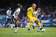 Burton Albion  forward Liam Boyce(27) challenged by Gillingham FC defender Gabriel Zakuani (6) (left) and Gillingham FC midfielder Mark Byrne (33) (right) during the EFL Sky Bet League 1 match between Gillingham and Burton Albion at the MEMS Priestfield Stadium, Gillingham, England on 11 August 2018.