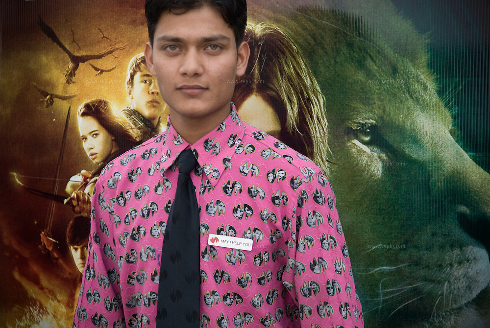 Vikas (21), a cafeteria worker at wave cinema complex, standing in front of a movie poster for a recent movie at Center Stage Mall in Noida.