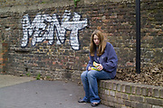 A teenage girl hanging out on the street, rolling a cigarette, UK 2008
