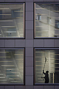 A workman wipes the ceiling of a vacant office building in the City of London.