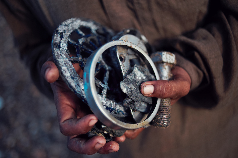 A scavenger holds scrap metal at the Gaddani Ship Breaking Yard, Balochistan Province, Pakistan on August 17, 2011. They once earned 7,000 Pakistani rupees($80 USD) in one day scavenging for metal. .