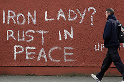 A pedestrian walks past graffiti that reads 'Iron Lady? Rust in Peace' referring to former British prime minister Margaret Thatcher in west Belfast, Northern Ireland, on 9th April, 2013 a day following Thatcher's death. Britain stood deeply divided over the legacy of former prime minister Margaret Thatcher as it made preparations for the grand funeral next week of the woman known around the globe as the 'Iron Lady', Belfast, Great Britain, 9th April, 2013.  Photo by Paul McErlane / i-Images. ..<br />