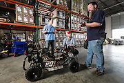 01/14/2016 133355 -- Garland, TX -- © Copyright 2016 Mark C. Greenberg<br /> <br /> From left: President and COO Rick Sukkar and CEO Alex Keechleof talk with warehouse manager Kevin Sadler in the warehouse of Garland, Texas based Monster Moto