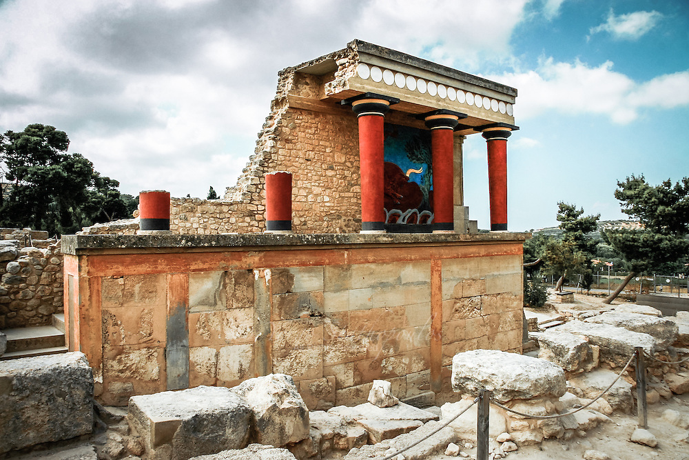 Restored North Entrance with charging bull fresco. The name Knossos survives from ancient Greek references to the major city of Crete. The identification of Knossos with the Bronze Age site is supported by tradition and by the Roman coins that were scattered over the fields surrounding the pre-excavation site, then a large mound named Kephala Hill, elevation 85 m (279 ft) from current sea level. Many of them were inscribed with Knosion or Knos on the obverse and an image of a Minotaur or Labyrinth on the reverse, both symbols deriving from the myth of King Minos, supposed to have reigned from Knossos. The coins came from the Roman settlement of Colonia Julia Nobilis Cnossus, a Roman colony placed just to the north of, and politically including, Kephala. The Romans believed they had colonized Knossos. After excavation, the discovery of the Linear B tablets, and the decipherment of Linear B by Michael Ventris, the identification was confirmed by the reference to an administrative center, 𐀒𐀜𐀰, ko-no-so, Mycenaean Greek Knosos in Linear B, undoubtedly the palace complex. The palace was built over a Neolithic town. During the Bronze Age, the town surrounded the hill on which the palace was built.<br /> <br /> The site was discovered in 1878 by Minos Kalokairinos (Μίνως Καλοκαιρινός). The excavations in Knossos began in AD 1900 by the English archaeologist Sir Arthur Evans (1851- 1941) and his team, and they continued for 35 years. The palace was excavated and partially restored under the direction of Arthur Evans in the earliest years of the 20th century. Its size far exceeded his original expectations, as did the discovery of two ancient scripts, which he termed Linear A and Linear B, to distinguish their writing from the pictographs also present. From the layering of the palace Evans developed de novo an archaeological concept of the civilization that used it, which he called Minoan, following the pre-existing custom of labelling all objects from the loca