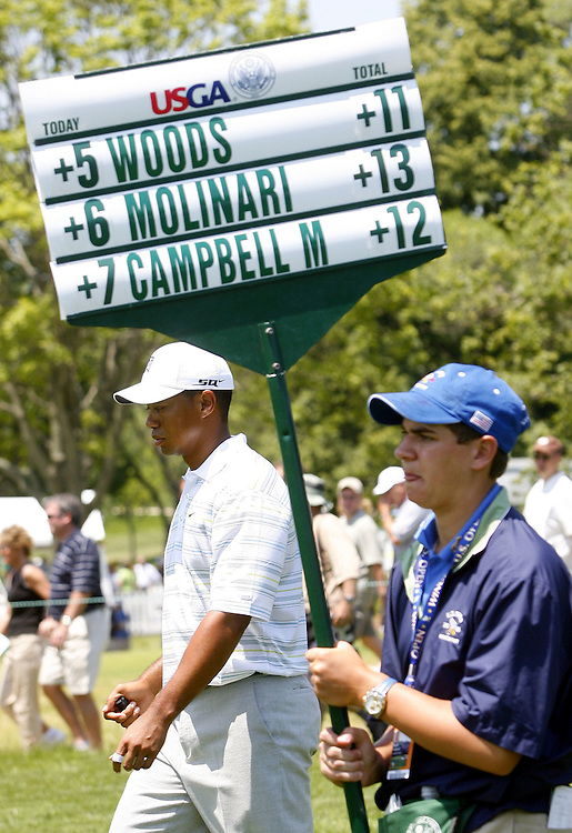 Tiger Woods of the US walks next to a boy carrying a scoreboard as he walks up the ninth hole (his final hole of the round) on the second day of the US Open Golf Championship at Winged Foot Golf Club in Mamaroneck, New York Friday, 16 June 2006.  Woods finished with a score of 152 for the two days (+6 each day for a total of +12) which is projected to be two strokes beyond the cut.