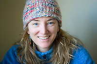 Smiling portrait of a late 30's woman in a knit hat and fleece jacket with long blond hair<br />