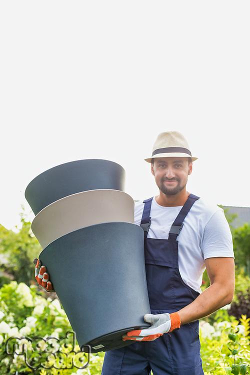 Portrait of mature gardener carrying pots in shop