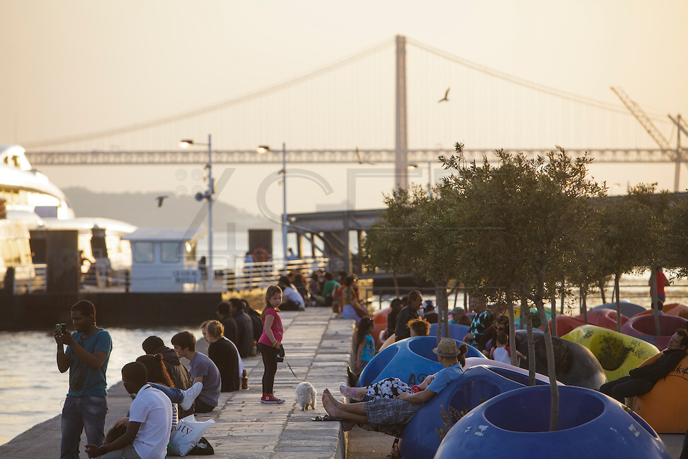 People enjoying sunset by Tagus riverside in Lisbonat Cais do Sodré district.