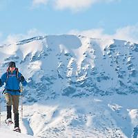 man snowshoeing in glacier national park,