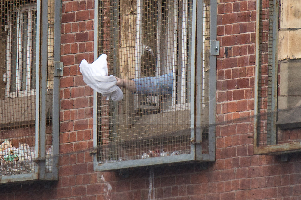 © Licensed to London News Pictures . 14/09/2015. Manchester, UK. A prisoner waves a white towel around outside his window at HMP Manchester (formerly Strangeways Prison ) , where Stuart Horner is conducting a rooftop protest against prison conditions , which has lead to prisoners activities being restricted . Photo credit : Joel Goodman/LNP