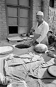 Man making bread and boys hanging around in market