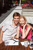 Young couple sitting at outdoor cafe portrait