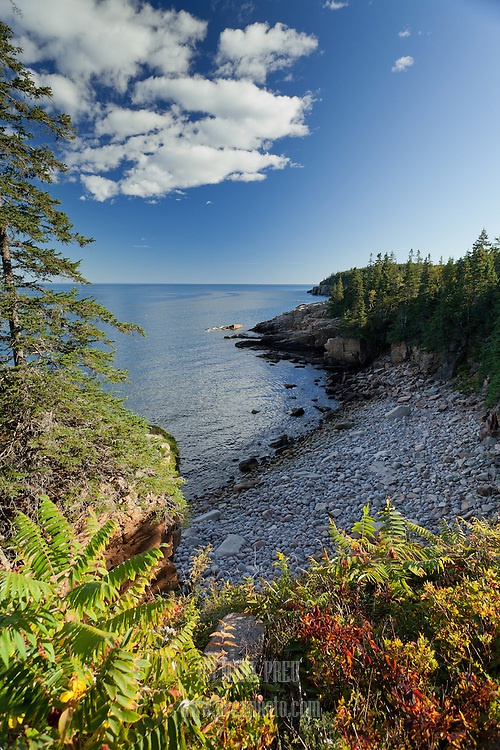 A cobble beach seen from the footpaththat parallels the park loop road in Acadia National Park.  In the distance are the Otter Cliffs.