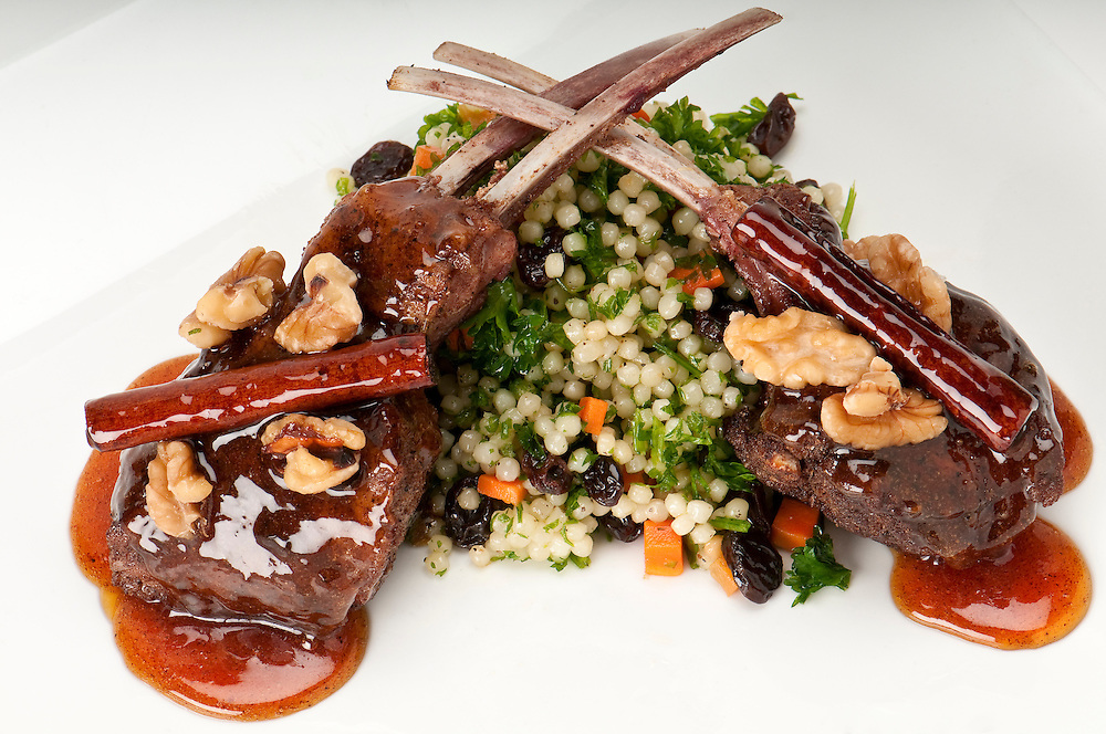 Close up of lamb chops with couscous and vegetables with a sauce of caramel, pepper and spices.