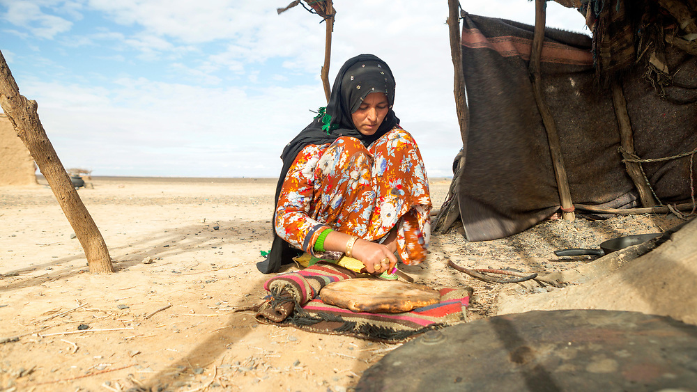 Nomadic family prepare madfouna - the Berber pizza - at their camp located along the fringes of the Erg Chebbi dunes, 40km from the Algerian border (Merzouga and Taous region), Southern Morocco, 2017-12-17.
