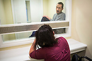 A prisoner on a closed visit sits talking to his wife. Closed visits take place in locked rooms with a toughened glass window between the prisoner and his visitor.  HMP/YOI Portland, Dorset. A resettlement prison with a capacity for 530 prisoners. <br /> &copy; prisonimage.org.  Any image use must be agreed first. All images must be properly credited.