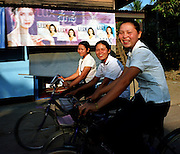 Three Laotian girls cycle past an advertisement advertising Thai soap in Vientiane Prefecture. Many Thai products are exported to Laos, which has limited manufacturing capabilities.