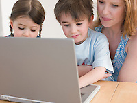 Mother Helping Children Use Laptop