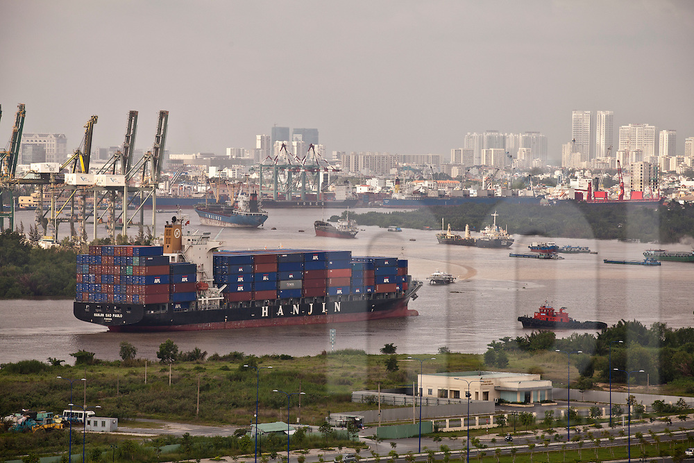 Container vessel approaching the port of Saigon. View above the Harbor and cityscape in background with skyscrapers of  Ho Chi Minh city (HCMC), Vietnam, Asia