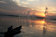 At the end of the day, as the sun sets on Dal Lake, a man rows his boat near scenic fountains.