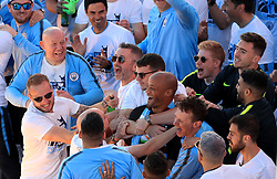 Manchester City's Vincent Kompany is mobbed on stage during the trophy parade in Manchester.