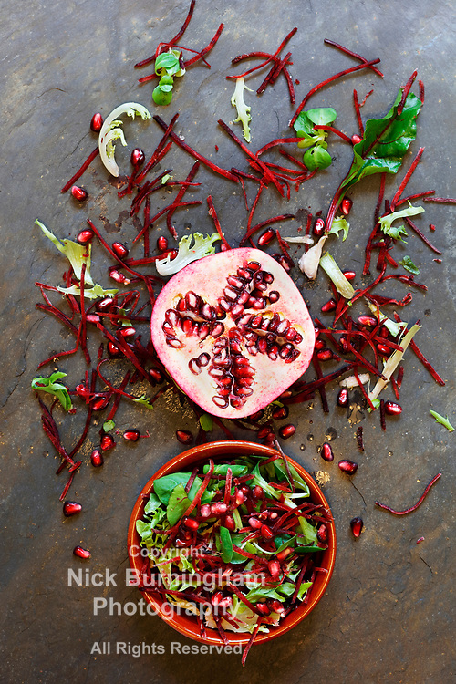 Ingredients for a healthy pomegranate salad with red cabbage, spinach , lettuce, rocket and pomegranate seeds