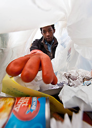 Ryan Grant reaches into  bag of trash during Garbology on Red Square, where grash from different locations is sorted to determine how much is recycleable or compostable at PLU on Tuesday, March 17, 2015. (Photo: John Froschauer/PLU)
